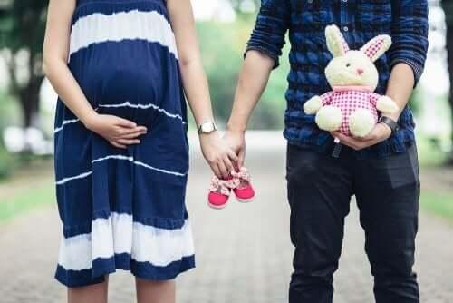 孕婦和男人牽手和嬰兒鞋